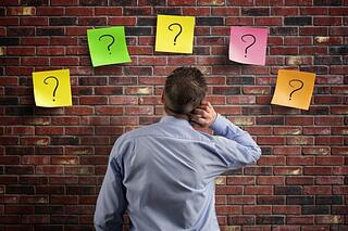 man_trying_to_decide_question_marks