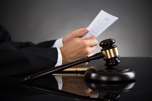 503873306_judge holding papers in wrongful death lawsuit