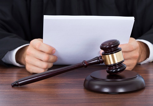 514218405_Judge reviewing bankruptcy papers in court
