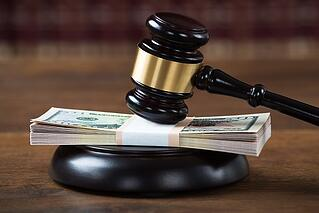 courtroom gavel with money