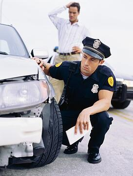 police_officer_examining_car_involved_in_accident