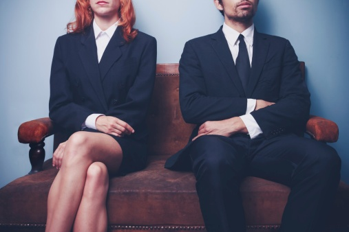 Couple in suits waiting for a lawyer.