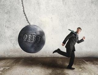 "Man running from a wrecking ball labeled ""debt."""