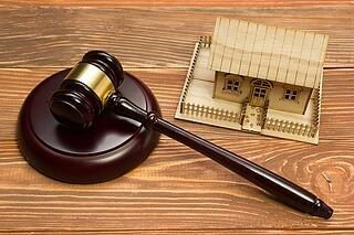 A gavel and a small model of a house.