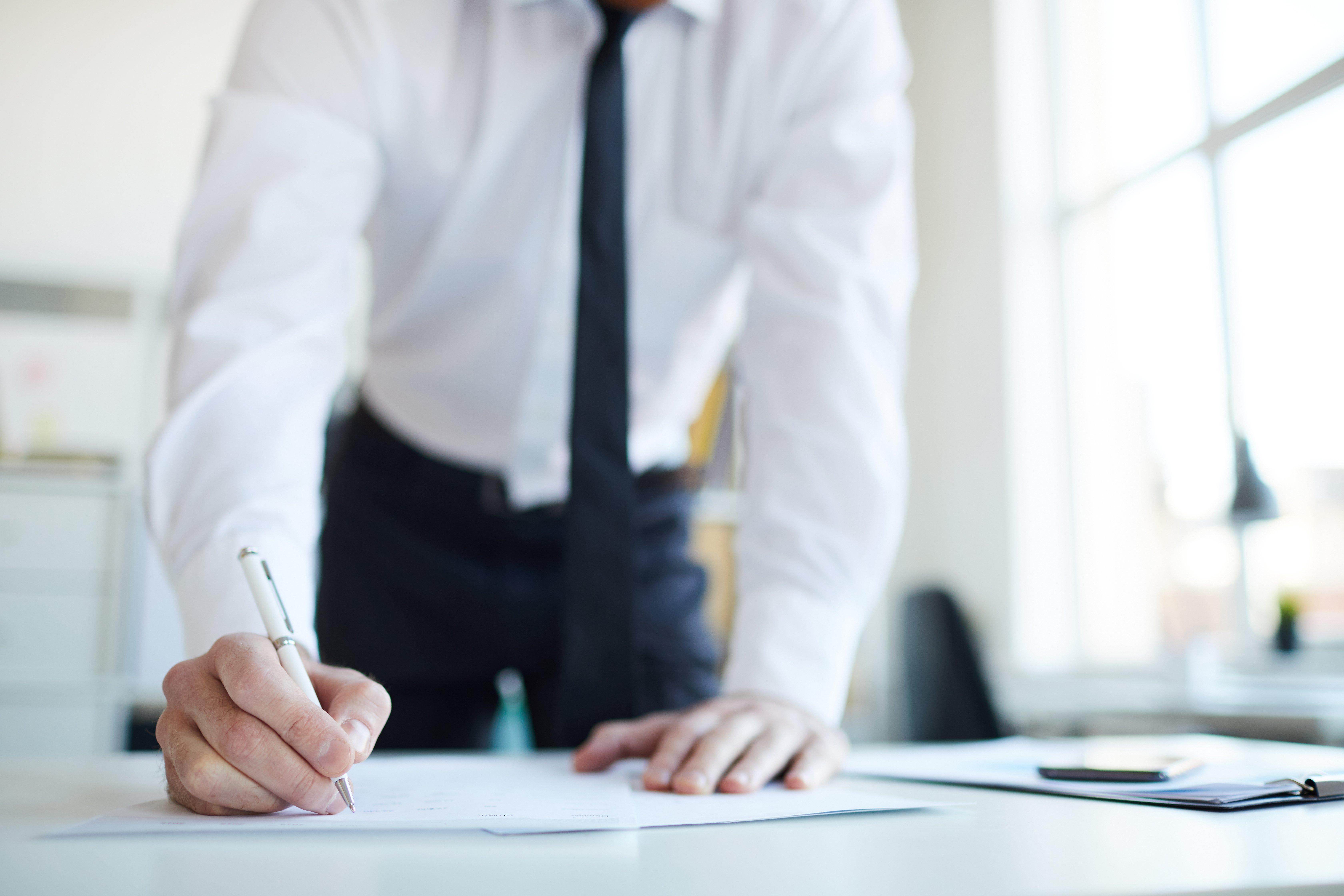 businessman-putting-signature-on-paper